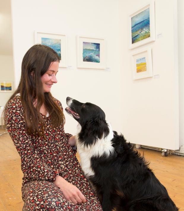 Jordyn Lynch, curator of the Sherkin Island community art exhibition getting a lending paw from her dog, Rufus. ©RobbieMurphy
